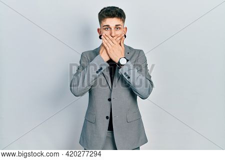 Young caucasian boy with ears dilation wearing business jacket shocked covering mouth with hands for mistake. secret concept.