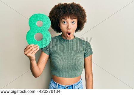 Young hispanic girl holding number eight scared and amazed with open mouth for surprise, disbelief face