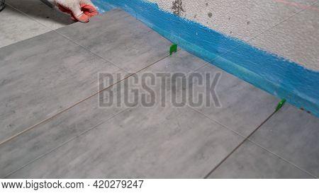 Installing Ceramic Tiles On The Floor. Home Improvement, Renovation - Construction Worker Tiler Is T
