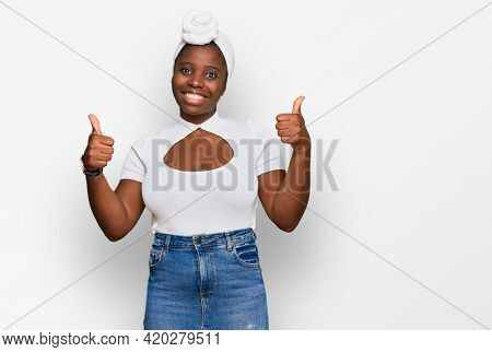 Young african woman with turban wearing hair turban over isolated background success sign doing positive gesture with hand, thumbs up smiling and happy. cheerful expression and winner gesture.