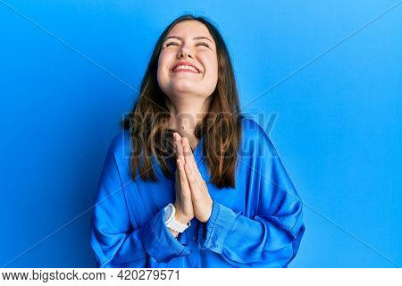 Young brunette woman wearing casual blue shirt begging and praying with hands together with hope expression on face very emotional and worried. begging.