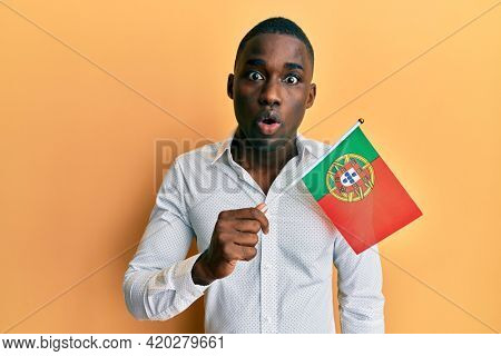 Young african american man holding portugal flag scared and amazed with open mouth for surprise, disbelief face