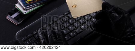 Burglar With A Stolen Credit Card. Hands In Glove On Laptop Keyboard With Credit Card