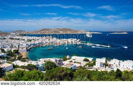 View of Mykonos town Greek tourist holiday vacation destination with famous windmills, and port with boats and yachts. Mykonos, Cyclades islands, Greece