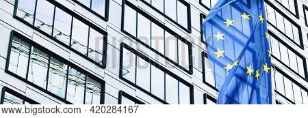 European Union Flag Waving In Front Of Modern Corporate Office Building, Symbol Of Eu Parliament, Co