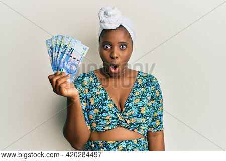 Young african woman wearing hair turban holding south african 100 rand banknotes scared and amazed with open mouth for surprise, disbelief face