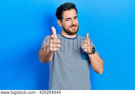 Handsome caucasian man with beard wearing casual striped t shirt pointing fingers to camera with happy and funny face. good energy and vibes.