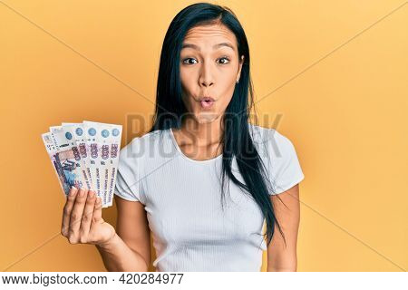 Beautiful hispanic woman holding 500 russian ruble banknotes scared and amazed with open mouth for surprise, disbelief face