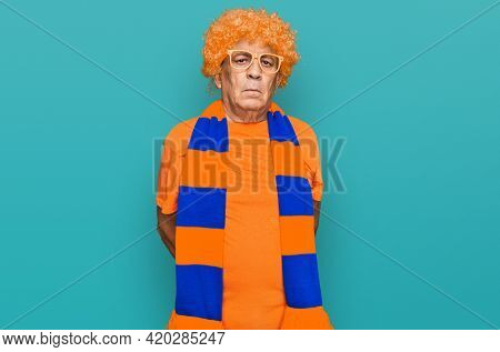 Senior hispanic man football hooligan cheering game with serious expression on face. simple and natural looking at the camera.