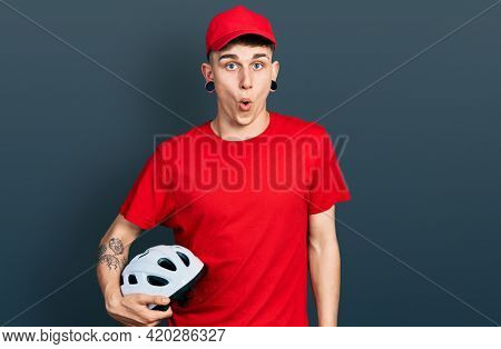 Young caucasian boy with ears dilation wearing delivery uniform and cap holding bike helmet scared and amazed with open mouth for surprise, disbelief face