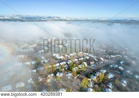 foggy spring morning over residential area of Fort Collins in northern Colorado after heavy rain and snow, aerial view with Front Range of Rocky Mountains in background