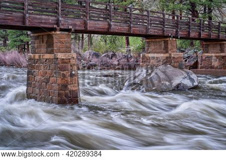 Poudre River under Greyrock trail bridge in a canyon above Fort Collins, Colorado, rainy spring scenery with high flow