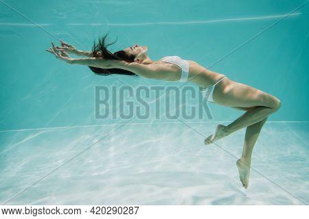 Peaceful Young Woman In White Swimwear Swimming In Pool.