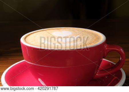 Cup Of Cappuccino In Red On Desk