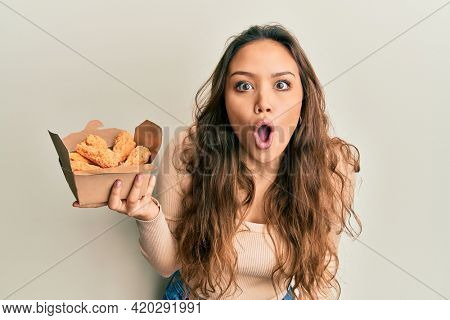 Young hispanic girl eating chicken wings scared and amazed with open mouth for surprise, disbelief face
