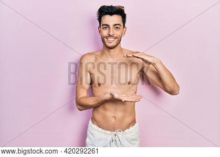 Young hispanic man wearing swimwear shirtless gesturing with hands showing big and large size sign, measure symbol. smiling looking at the camera. measuring concept.