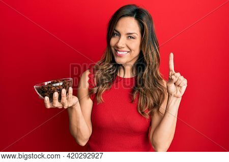 Young latin woman holding bowl with raisins smiling happy pointing with hand and finger to the side
