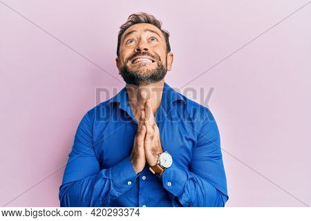 Middle age man wearing casual clothes begging and praying with hands together with hope expression on face very emotional and worried. begging.