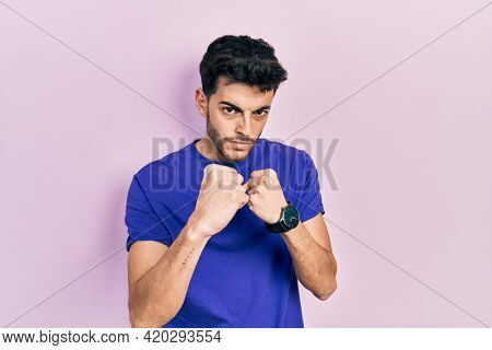 Young hispanic man wearing casual t shirt ready to fight with fist defense gesture, angry and upset face, afraid of problem