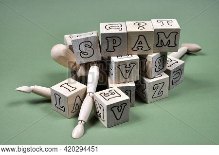 The Concept Of The Problem Of Receiving Spam. A Wooden Man Littered With Cubes And The Inscription S