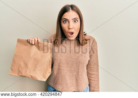 Young beautiful woman holding take away paper bag scared and amazed with open mouth for surprise, disbelief face