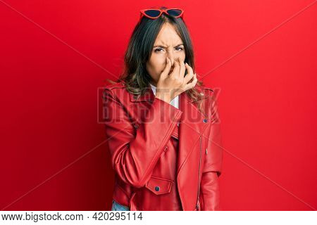 Young brunette woman wearing red leather jacket smelling something stinky and disgusting, intolerable smell, holding breath with fingers on nose. bad smell