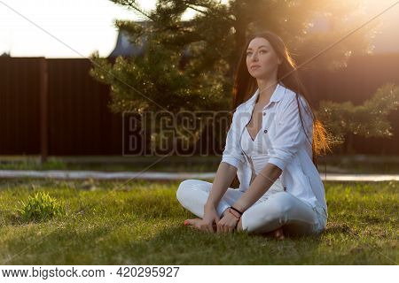 A Young Woman  Sits Relaxed In A White Top, Shirt And Jeans On The Green Grass In The Park On A Warm