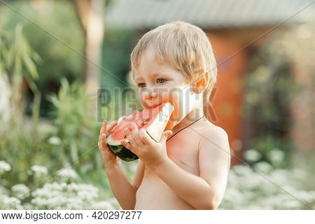 Portrait Of Cute Handsome In Nature. Funny Kid Eating Watermelon Outdoors In Summer Park. Happy Chil