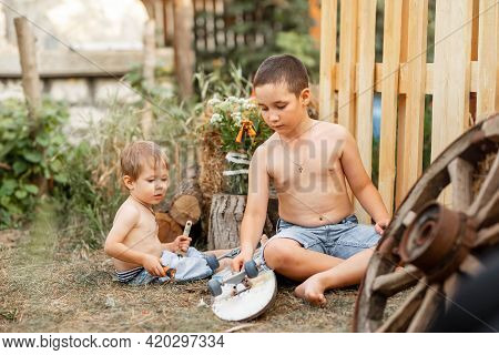 Smiling Beautiful Family On The Backyard Lawn. Childs Expression. Two Happy Little Boys Playing In T