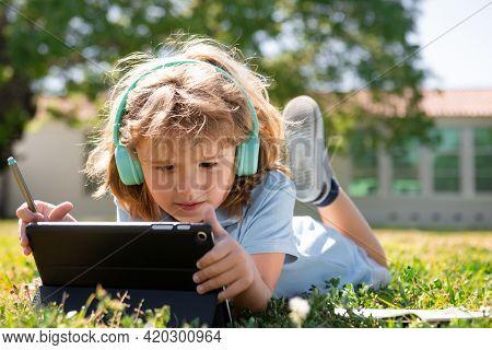 Portrait Of Cute Smart Clever School Boy Nerd Doing Homework Outside. Kid Distance Learning Concept.