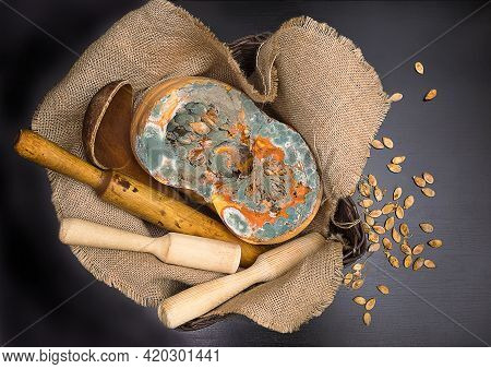 Orange Moldy Cut Of A Pumpkin Surrounded By Kitchen Utensils On Sackcloth And Scattered Seeds On A B
