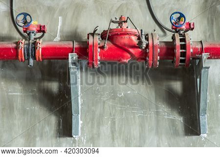 Red Water Or Gas Pipeline With Gate Pressure Valve On Concrete Wall. Industrial Tubes And Valves, Li