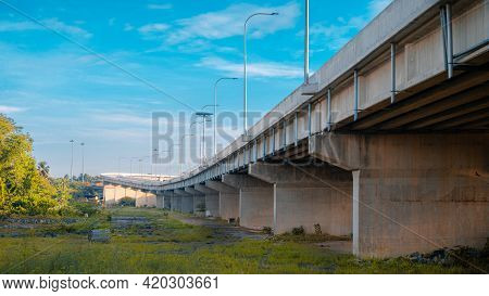 Underneath The Elevated Expressway Concrete Structure, Greenery, And Clear Blue Skies Landscape View