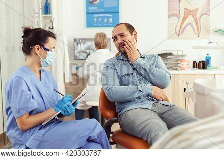 Stomatologist Nurse Explaining Medical Procedure To Sick Patient