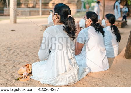 Buddhist Female Devotees Worshipping At Jaya Sri Maha Bhodi While Sitting On The Sandy Soil In White