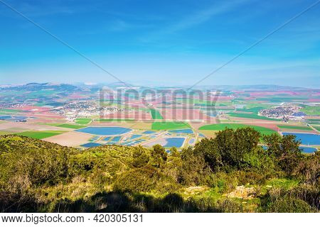 Jezreel Valley in the Lower Galilee, Israel. The valley is now occupied by fertile farmland belonging to kibbutzim, moshavim and Arab villages. Warm winter in israel. Picturesque agricultural fields