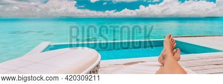 Luxury vacation swimming pool banner background. Woman lying down relaxing on lounger sunbathing legs and feet in summer sun. Travel holiday panoramic.