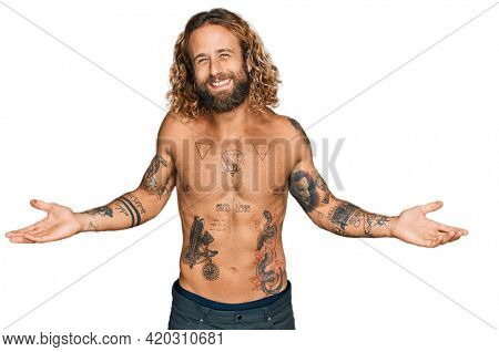 Handsome man with beard and long hair standing shirtless showing tattoos smiling showing both hands open palms, presenting and advertising comparison and balance