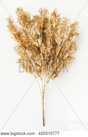 Artificial gold fern leaves on an off white background