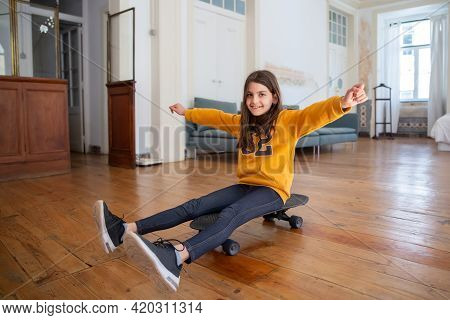 Happy Brunette Girl Sitting On Skateboard, Having Fun At Home. Cheerful Caucasian Kid Sitting On Lon