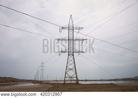 Desert Landscape With Transmission Towers . They Laid The Railway Lines On Top Of Each Other. A Smal