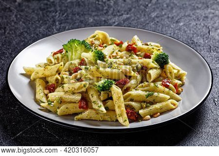 Broccoli Pesto Penne Pasta With Sundried Tomatoes And Pine Nuts On A Plate, Horizontal View From Abo