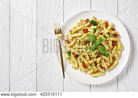Broccoli Pesto Penne Pasta With Sundried Tomatoes And Pine Nuts On A Plate On A  White Wooden Table,