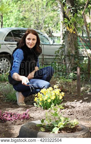 Young Happy Brunette Girl Works In A Spring Garden, Plants Flowers And Soil Grab With Special Rakes