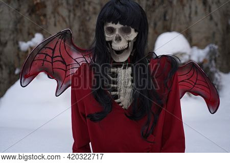 Devil Bride Skeleton With Red Dress And Devil Wings In Snow