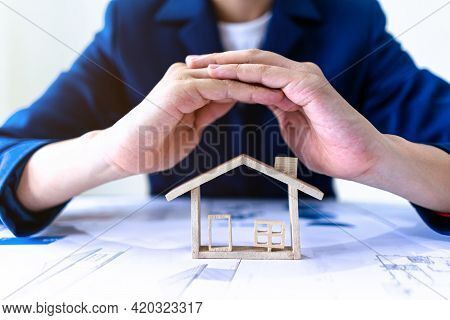 Real Estate Agent Or Insurance Agent Making Gestures To Protect House Model. Property Housing Insura