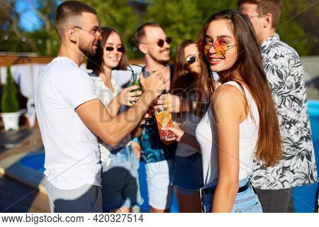 Pretty Woman Having Fun At Poolside Summer Party Clinking Glasses With Friends On Sunny Summer Day N
