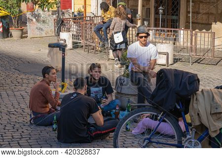 Rome, Italy - March 28, 2021, Group Of Young People Sitting On Paving Stones During A Pandemic (covi