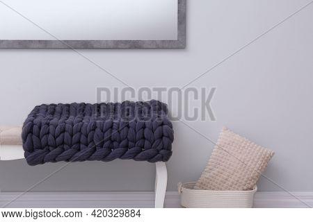 Knitted Merino Wool Plaid On Bench Near Grey Wall