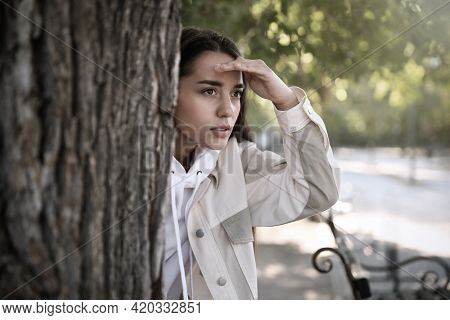 Young Woman Spying On Her Boyfriend In Park. Cheating Concept